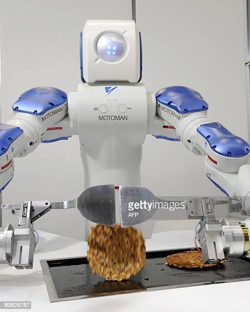 Japanese giant Yaskawa Electric's industrial robot Motoman turns over an 'okonomiyaki' a Japanese pancake on a hot plate for a demonstration of...