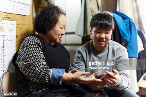japanese girl and her grandmother looking at the cell phone - makiko tanigawa ストックフォトと画像