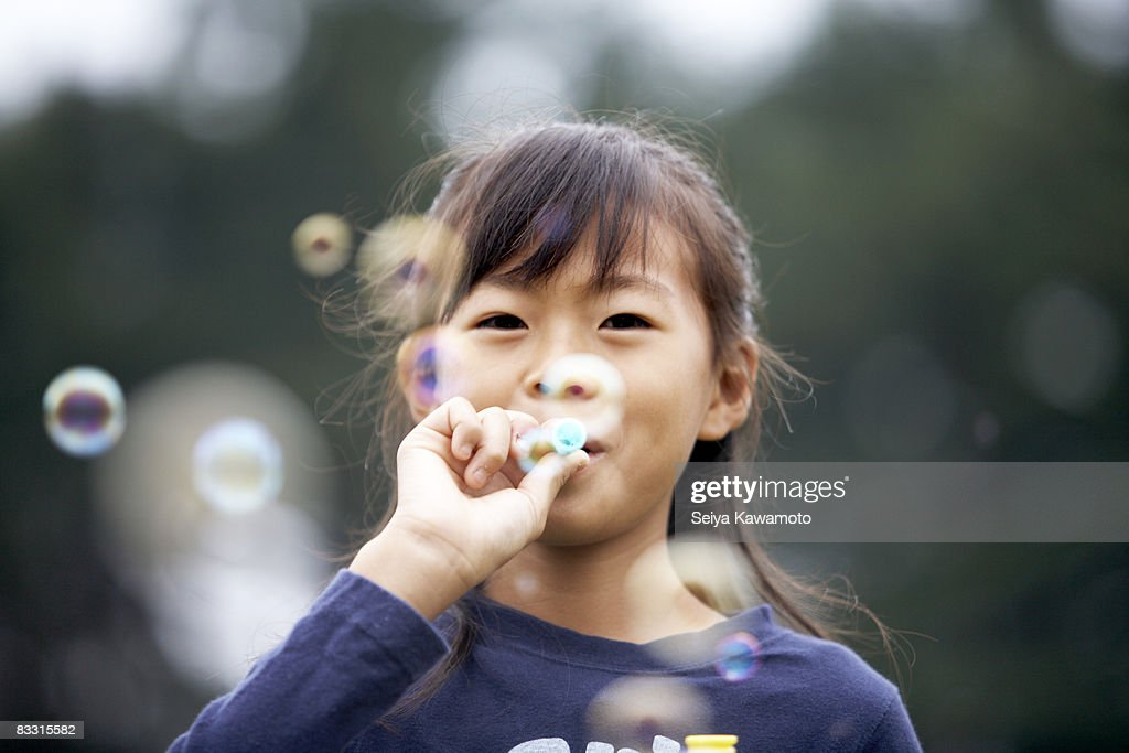 Japanese girl blowing bubbles : Stock Photo