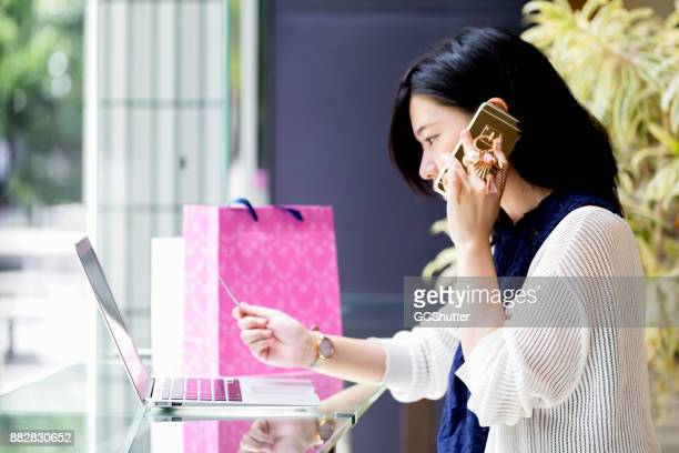 japanese girl calling her bank after a trouble with her credit card - credit score stock pictures, royalty-free photos & images