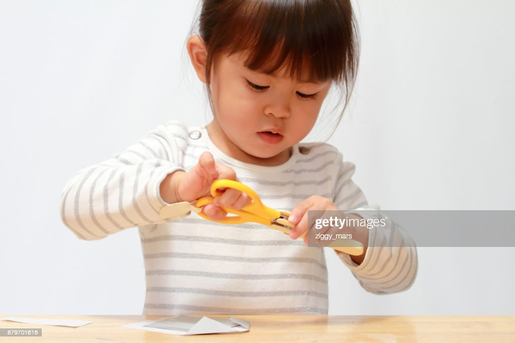 Japanese girl cutting paper with scissors (3 years old) : Stock Photo