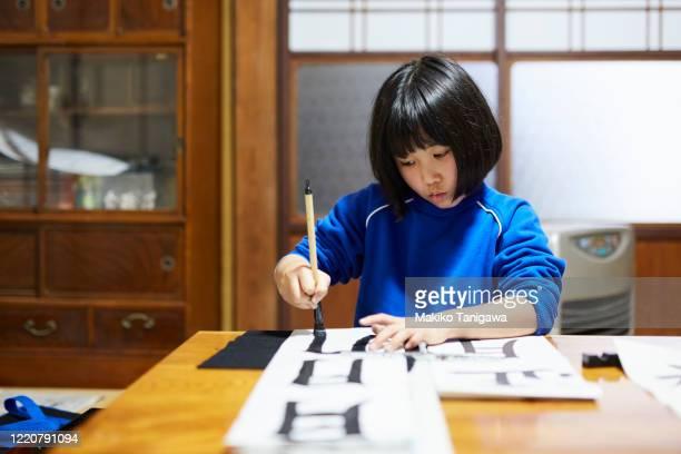 japanese girl doing kakizome - 書道 ストックフォトと画像