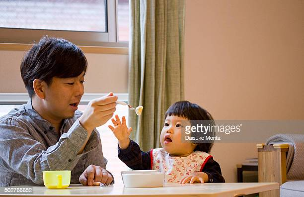 Japanese girl having lunch at table with her father
