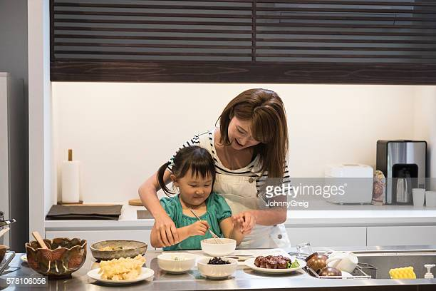 Japanese girl helping mother in the kitchen