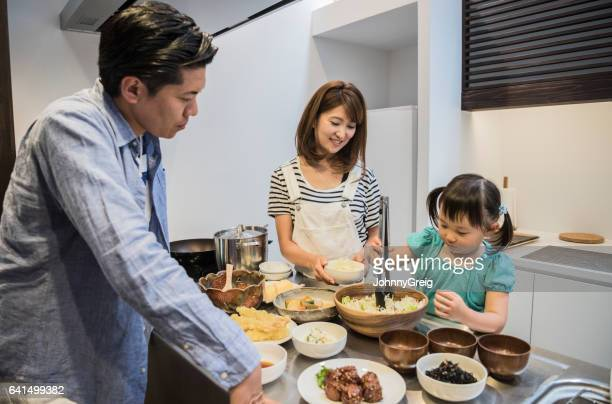 Japanese girl helping parents in kitchen