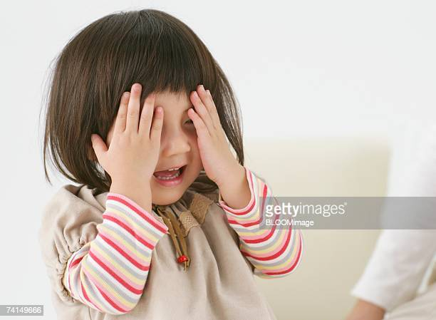 Japanese girl hiding face with hands