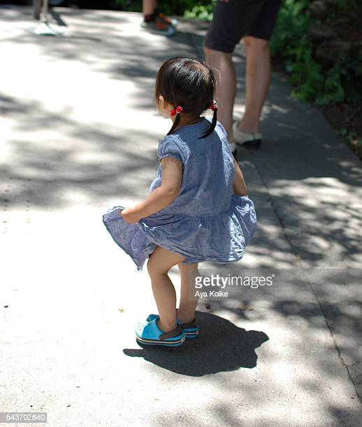 A Japanese girl, playing with her skirt under the sunlight of summer