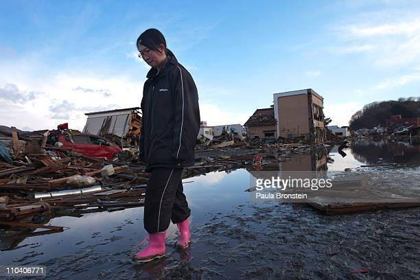 Japanese girl reacts while standing amongst the rubble where her home had been while visiting it for the first time on March 18 2011 in Kesennuma...