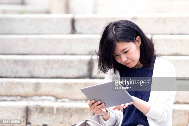 Japanese girl seated on a public park steps and using her digital tablet