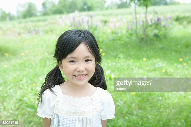 Japanese girl (5-6) smiling on field