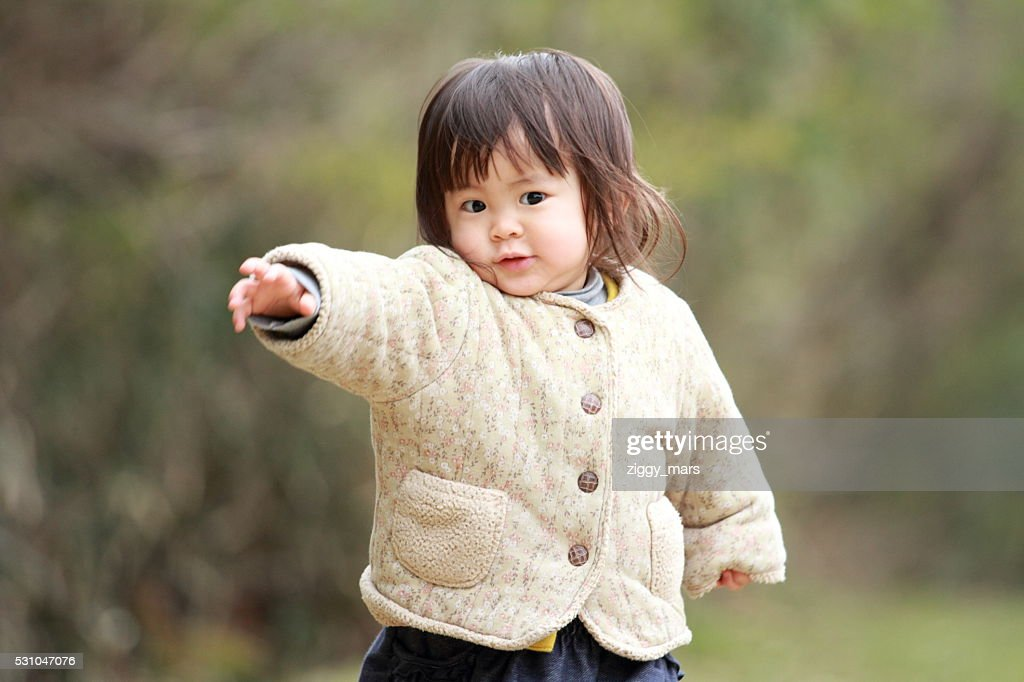 Japanese girl walking on the grass (1 year old) : Stock Photo