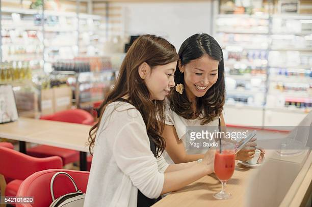 Japanese girlfriends looking at a smart phone.