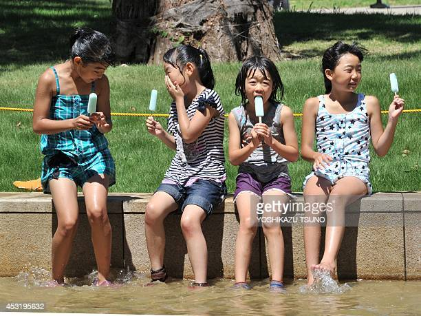 Japanese girls eat popsicles at a park in Tokyo on August 5 2014 Sweltering summer heat in Japan has left at least 7 people dead over the past week...