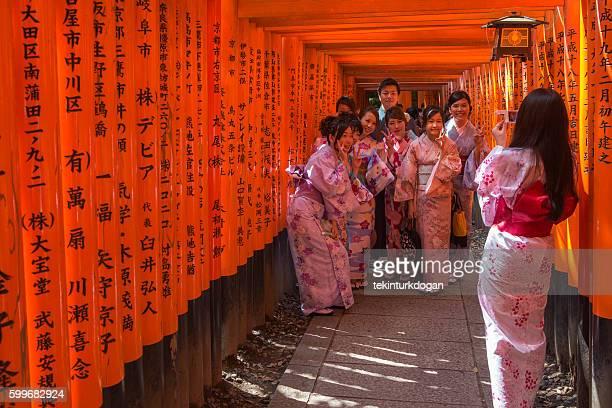 japanese girls posing in gates of Fushimi-Inari temple  kyoto japan