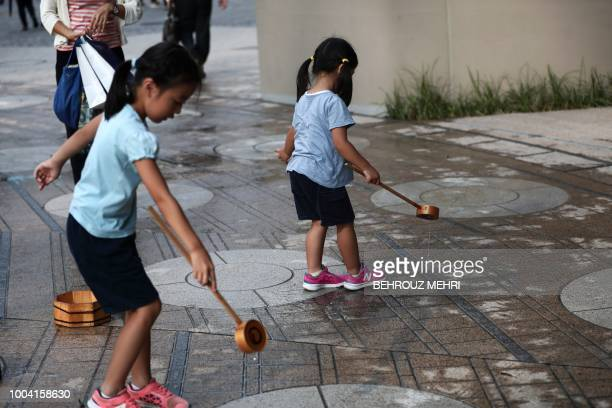 Japanese girls splash water on the ground during a water sprinkling event called Uchimizu which is meant to cool down the area in Tokyo on July 23...