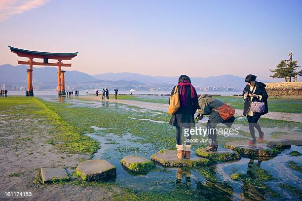 Japanese girls touring Miyajima Island cross a stone path in shallow water in front of the renowned giant, red torii gate at Itsukushima Shinto...