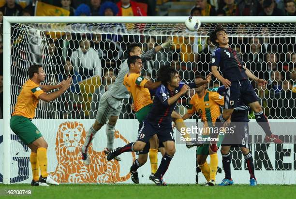 Japanese goalkeeper Eiji Kawashima punches the ball away from Tim Cahill of Australia during the FIFA World Cup Asian Qualifier match between the...