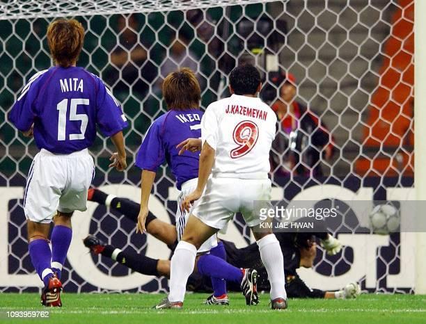 Japanese goalkeeper Yosuke Fujigaya dives as he misses Iran's Javad Kazemeyan first goal as Hikaru Mita and Shohei Ikeda look on during the football...