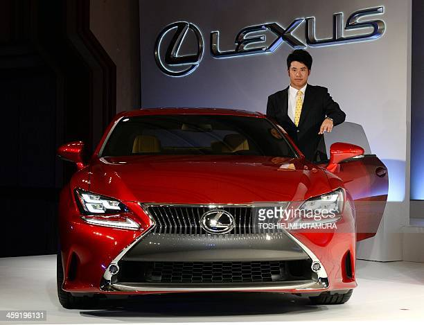 Japanese golfer Hideki Matsuyama stands beside a Lexus sports coupe RC during a press conference on his sponsorship with Lexus in Tokyo on December...