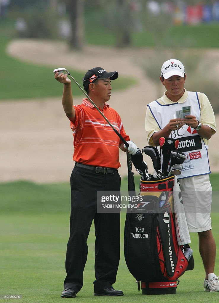 Japanese golfer Toru Taniguchi and his caddie prepare to hit at the 16th hall during the third round of the Dubai Desert Classic golf tournament 05 March 2005.