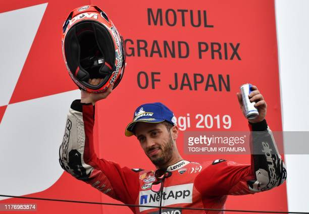 Japanese Grand Prix third placed Ducati Team rider Andrea Dovizioso of Italy acknowledges cheers on the podium after the MotoGP class Japanese...