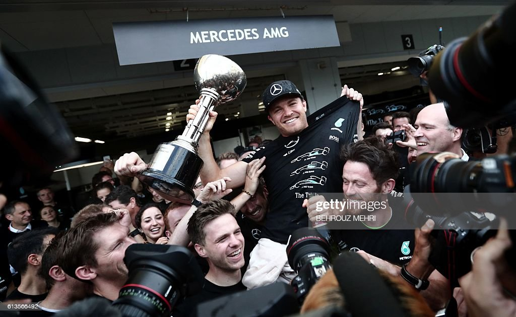 Japanese Grand Prix winner Mercedes AMG Petronas F1 Team's German driver Nico Rosberg holds his trophy as Mercedes AMG Petronas members celebrate at their paddock after the Formula One Japanese Grand Prix race in Suzuka on October 9, 2016. / AFP / BEHROUZ