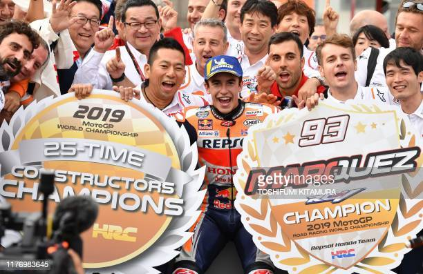 Japanese Grand Prix winner Repsol Honda Team rider Marc Marquez of Spain celebrates with his team officers at the parc ferme after the MotoGP class...