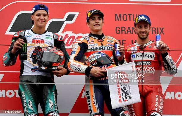Japanese Grand Prix winner Repsol Honda Team rider Marc Marquez of Spain poses with second placed Petronas Yamaha SRT rider Fabio Quartararo of...
