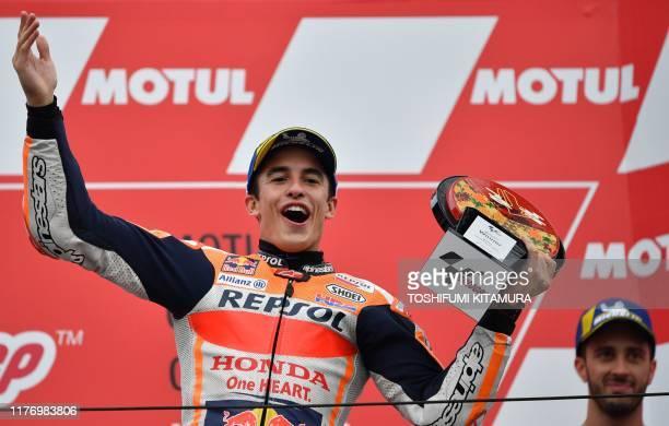Japanese Grand Prix winner Repsol Honda Team rider Marc Marquez of Spain celebrates on the podium while third placed Ducati Team rider Andrea...
