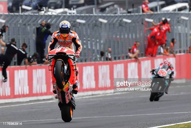 Japanese Grand Prix winner Repsol Honda Team rider Marc Marquez of Spain pops a wheelie to cross the finish line ahead of second placed Petronas...