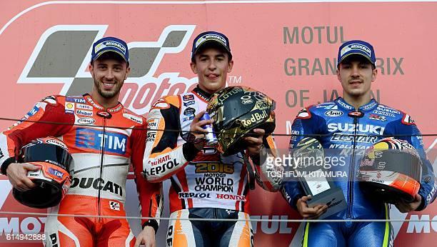 Japanese Grand Prix winner Repsol Honda Team's Spanish rider Marc Marquez poses with second placed Ducati Team's Italian rider Andrea Dovizioso and...