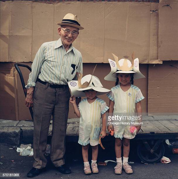 A Japanese grandfather and his two granddaughters wearing paper samurai hats in Chicago Illinois 1987