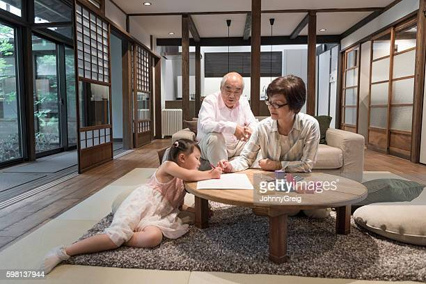 Japanese grandmother and grandfather at home with granddaughter
