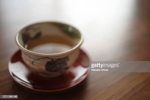 japanese green tea (sencha tea) in a cup ( shino-oribe ware) placed on chataku (shunkei-nuri wooden lacquered tea cup saucer) on wooden table ,selective focus - brown ストックフォトと画像