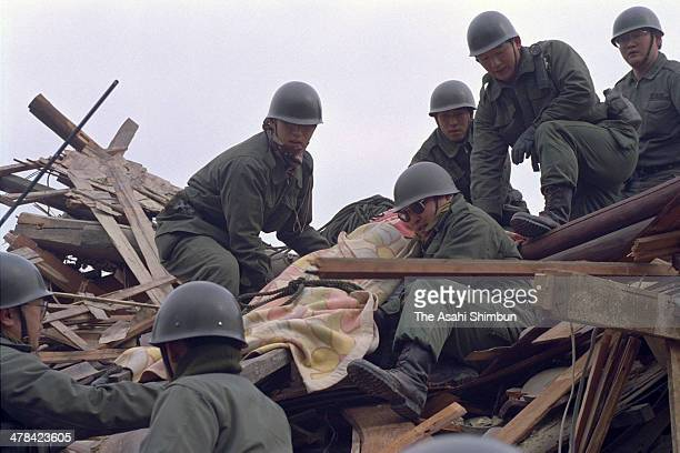 Japanese Ground SelfDefense Force members carry a body found at a collapsed house pm Janaury 18 1995 in Nishinomiya Hyogo Japan Magnitude 73 strong...