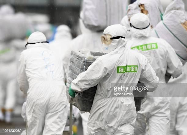 Japanese Ground SelfDefense Force personnel in hazmat suits take part in an operation to cull 6600 pigs at a pig farm in Toyota Aichi Prefecture...