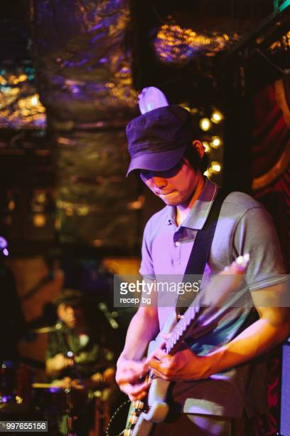 japanese guitarist playing the guitar at stage - modern rock stock pictures, royalty-free photos & images