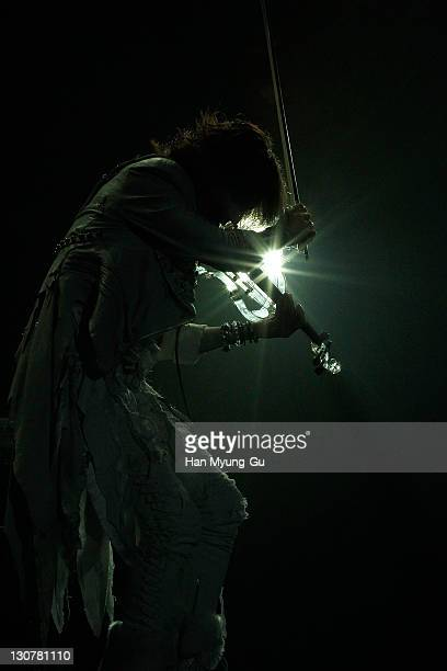 Japanese guitarist Sugizo of the band X Japan play violin performs during a concert at Olympic Gymnasium on October 28 2011 in Seoul South Korea