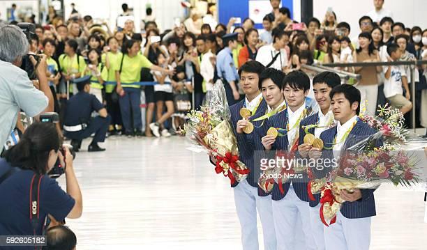 Japanese gymnasts Koji Yamamuro Kenzo Shirai Kohei Uchimura Ryohei Kato and Yusuke Tanaka pose for photographers with their gold medals at Narita...