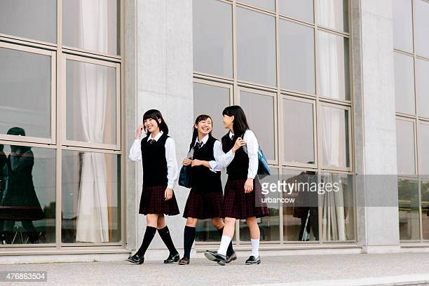 Japanese high school. Female students walk outside, building exterior