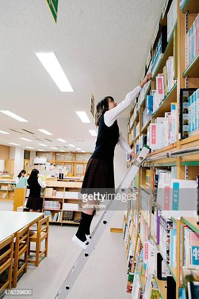 Japanese high school, library. Choosing a book, ladder