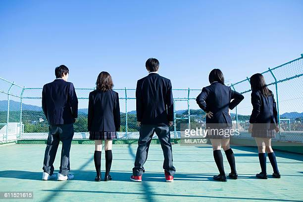 Japanese high school students stand on the roof