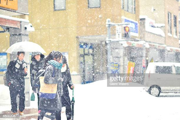 Japanese highschool students on there way home from school on a snowy, winter's day.