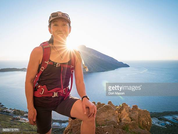 japanese hiker standing on hilltop over ocean - asian 50 to 55 years old woman stock photos and pictures