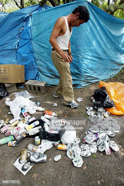 Japanese homeless man crushes aluminum cans in front of his hut made from blue plastic sheeting in an Osaka park. He collects aluminum cans from...