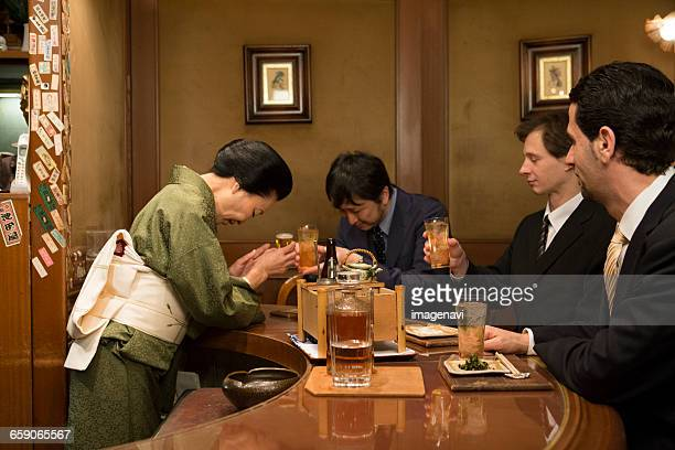 Japanese hostess toasting with businessman