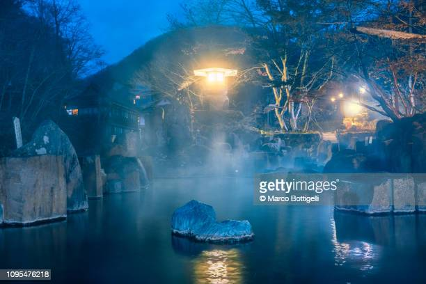 japanese hot spring (onsen) illuminated at dusk, japan - hot spring stock pictures, royalty-free photos & images
