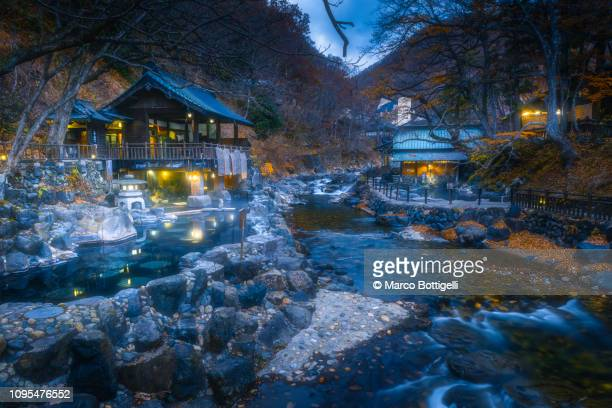 japanese hot spring (onsen) illuminated at dusk, japan - 宿屋 ストックフォトと画像