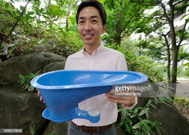 Japanese housing equipmentmaker Lixil marketing and technology director Daigo Ishiyama displays the company's SATO toilet system which features an...