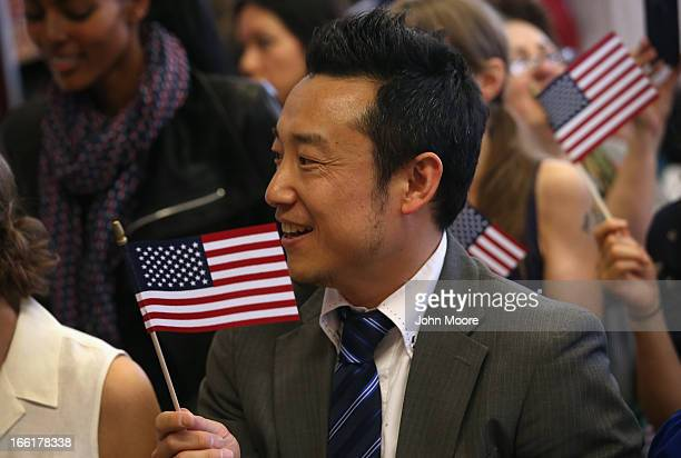 Japanese immigrant and new American citizen Shinichi Yabuki celebrates after taking the oath of citizenship at a naturalization ceremony on April 9...